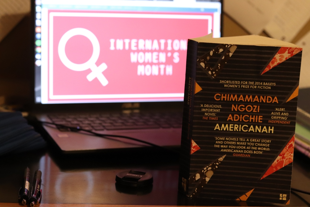 "The book in the front of a laptop with a wallpaper saying ""International Women's Month"""
